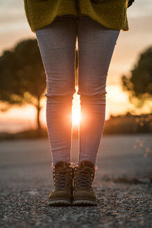 Woman wearing hiking boots standing on a road at sunset - KKAF00444