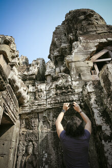 Cambodia, Angkor Wat, Angkor Thom, Bayon temple, tourist taking cell phone picture - REAF00206