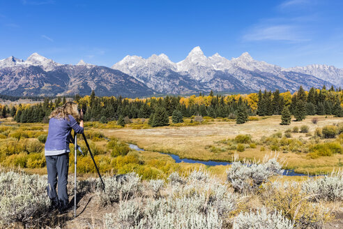 USA, Wyoming, Rocky Mountains, Grand Teton National Park, Snake River, Cathedral Group, woman taking picture of Teton Range - FOF08883