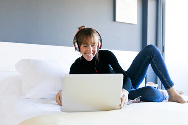 Smiling young woman lying on bed using laptop and wearing headphones - VABF01111