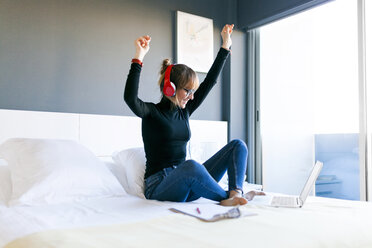 Happy young woman on bed with laptop wearing headphones - VABF01120