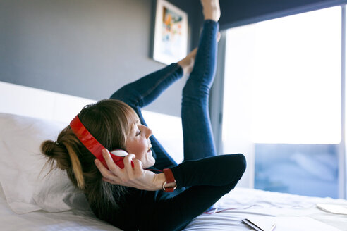 Happy young woman lying on bed wearing headphones - VABF01123