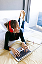 Young woman lying on bed using laptop and wearing headphones - VABF01126