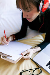 Young woman lying on bed writing on clipboard - VABF01129