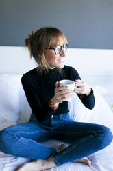 Young woman sitting on bed drinking cup of coffee - VABF01132