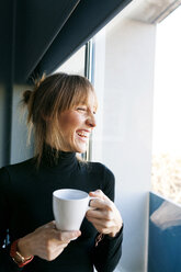 Happy young woman at home drinking cup of coffee looking out of window - VABF01138