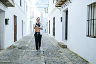 Young woman jogging in the street - KIJF01228