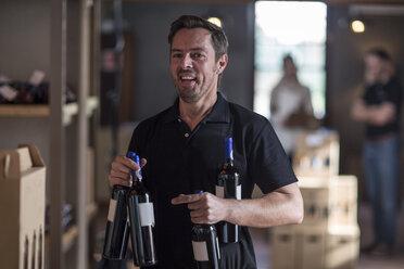 Portrait of smiling man holding wine bottles in shop - ZEF12854