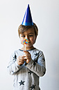Portrait of cross-eyed little boy with lollipop and blue party hat - VABF01144