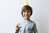 Portrait of little boy with yellow party hat holding lollipop between his teeth - VABF01147