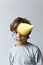 Portrait of little boy with yellow party hat on one eye - VABF01153