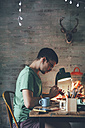 Young man painting animal figurine with paint - RTBF00665