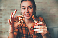 Young woman painting hippopotamus plastic figure with gold paint - RTBF00668