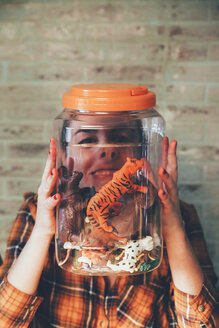 Funny woman pressing her face against jar with plastic animals - RTBF00671