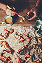 Overhead view of woman painting animal figurines with paint - RTBF00674