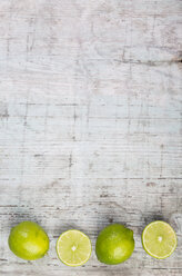 Row of whole and sliced limes on wood - JUNF00842