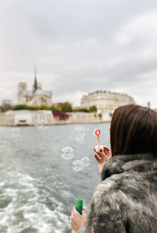 Paris, France, tourist taking a cruise on Seine River and blowing soap bubbles - MGOF02997