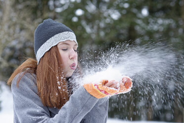 Teenage girl blowing snow out of her hands - LBF01562