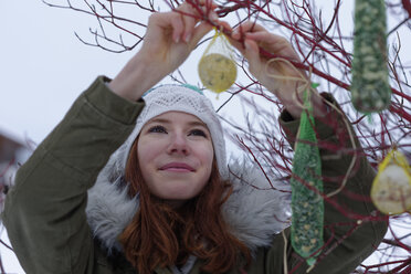 Portrait of smiling teenage girl hanging up fat balls in winter - LBF01568