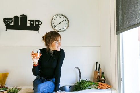 Young woman drinking fresh grapefruit juice in her kitchen - VABF01164