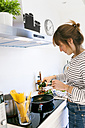 Young woman cooking vegan pasta in her kitchen - VABF01167