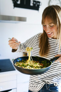 Young woman holding pan with vegan pasta dish - VABF01182