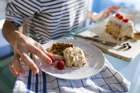 Young woman garnishing piece of vegan cake - VABF01197