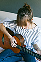 Young woman playing guitar, sitting on bed - VABF01203