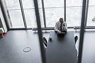 Senior manager in office using smartphone and laptop - UUF09917