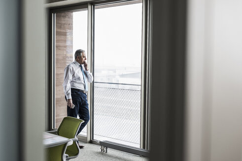 Senior manager in office standing at the window holding smartphone - UUF09920