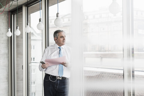 Senior manager in office standing at window talking on smartphone, holding document - UUF09938