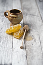 Honeycombs, clay pot and honey dipper on wood - MYF01874