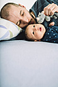 Father playing with his newborn baby girl and a a cuddly toy on bed - GEMF01485