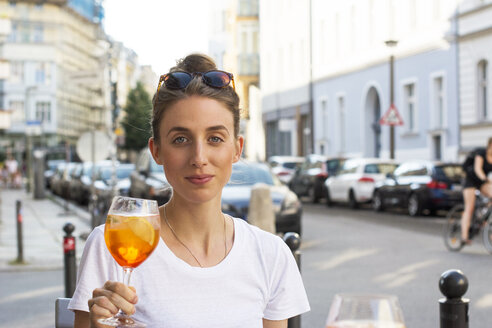 Portrait of young woman toasting with aperitive at pavement cafe - LMF00632