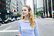 USA, New York, Manhattan, Young woman walking in the street, holding mobile phone - GIOF01891