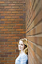 Portrait of a young woman leaning against brick wall - GIOF01900