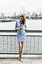USA, New York City, Young woman standing in Manhattan using smart phone - GIOF01906