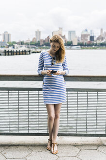 USA, New York City, Young woman standing in Manhattan using smart phone - GIOF01906