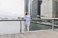 USA, New York City, Young woman standing in Manhattan at railing, holding smart phone - GIOF01912