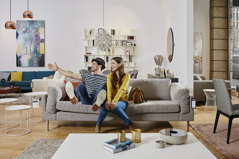 Couple in modern furniture store testing couch, being happy - RORF00582