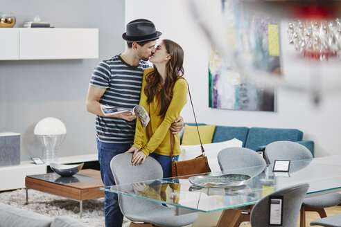 Couple in furniture store looking at dining table, kissing - RORF00585