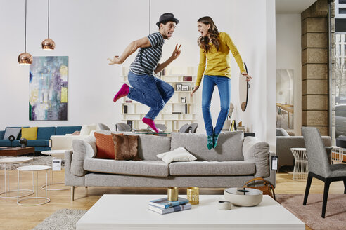 Couple in modern furniture store jumping on couch - RORF00588