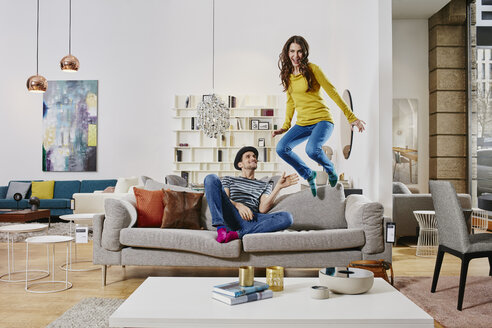 Couple in modern furniture store jumping on couch - RORF00591