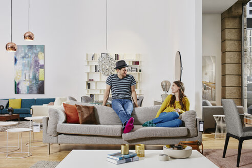 Couple in modern furniture store testing couch, being happy - RORF00594