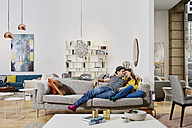 Couple in modern furniture store testing couch, being happy - RORF00597