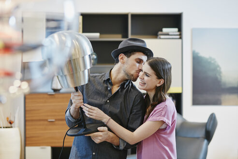 Couple in furniture store choosing lamp - RORF00627