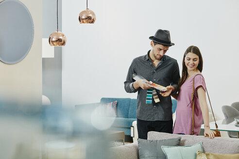 Couple in furniture store looking at color samples - RORF00636