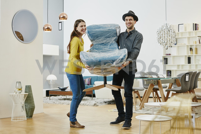 Happy couple carrying new arm chair out of furniture store - RORF00639 - Roger Richter/Westend61