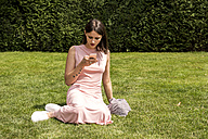 Young woman sitting on a meadow looking at cell phone - LMF00635