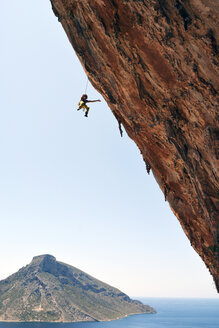 Greece, Kalymnos, climber abseiling in rock wall - LMF00670
